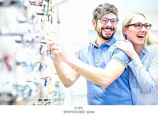Couple laughing near glasses rack in optometrist's shop
