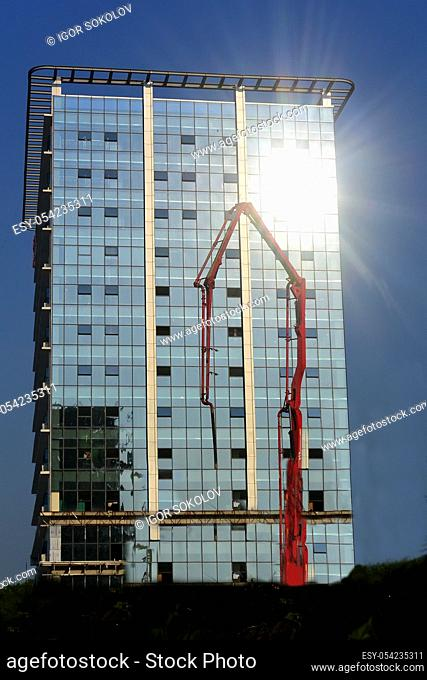 Red concrete pump against a glass tall building and blue sky, Cambodia