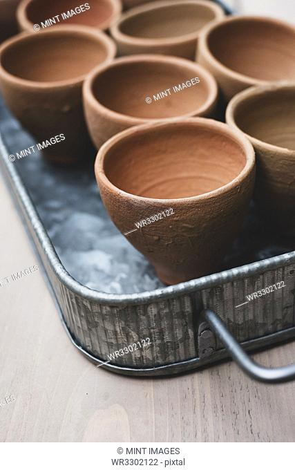High angle close up of terracotta plant pots on metal tray