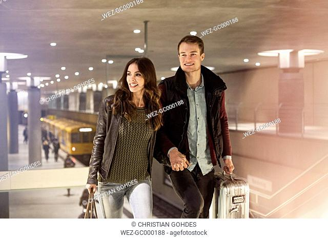 Germany, Berlin, smiling couple leaving underground station