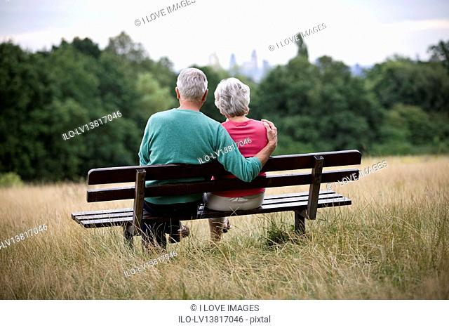 A senior couple sitting on a bench in a park, admiring the view