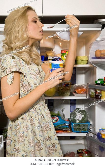 woman eating yogurt next to refrigerator