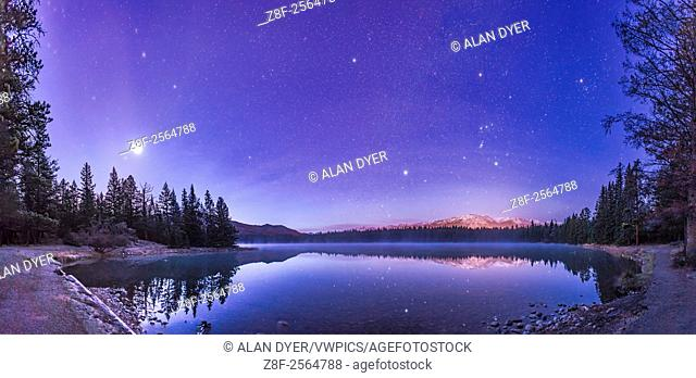 A panorama of roughly 120° showing a star- and planet-filled sky in the dawn twilight over Lake Annette in Jasper National Park, Alberta