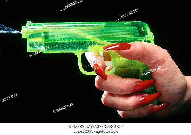 Woman with long red fingernails shooting green squirt gun