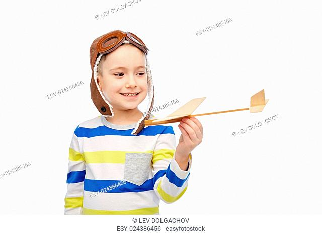 childhood, fashion and people concept - happy smiling little boy in aviator hat playing with wooden airplane