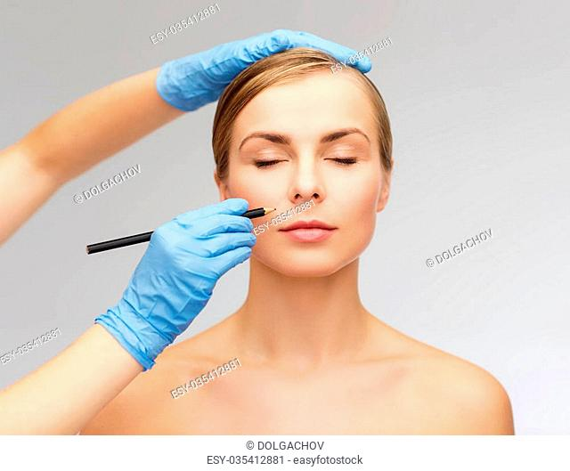 healthcare, beauty and medicine concept - beautiful woman face with closed eyes and beautician hands with pencil