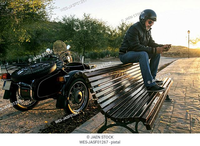 Biker wearing helmet and sunglasses sitting on backrest of a bench looking at smartphone