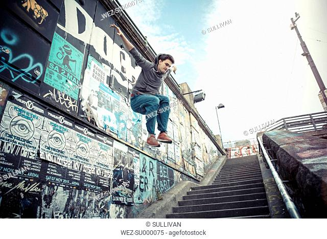 Young man jumping off wall
