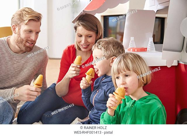 Happy family with popsicles and model car in living room