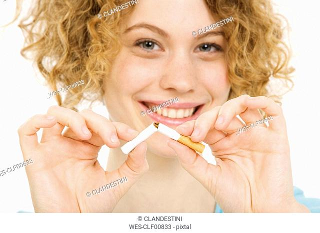 Young Woman breaking cigarette in half, smiling, portrait