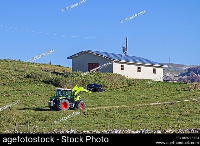 Landwirt mit Bulldog erledigt seine Arbeit auf der Hochfläche der Monti Lessiniberge