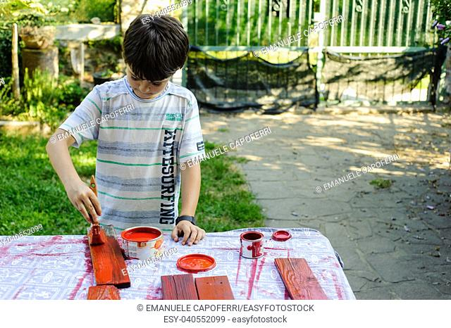 child painting of red wooden planks in his garden