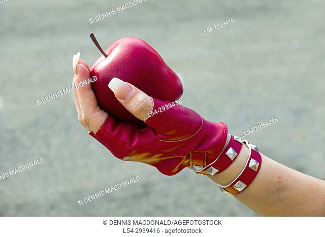 Female hand wearing a red glove holding an apple