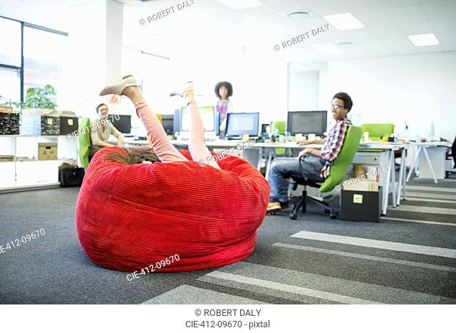 Businesswoman playing in beanbag chair in office