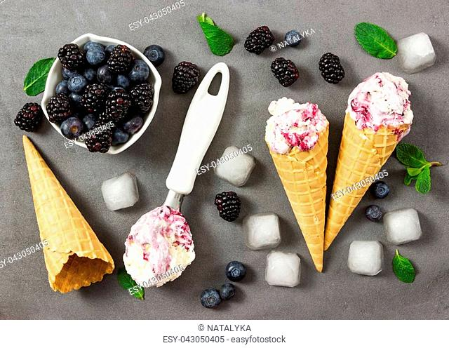Fruit ice cream with fresh blackberry and blueberry, ice cubes and empty ice cream cone on gray stone background. Top view