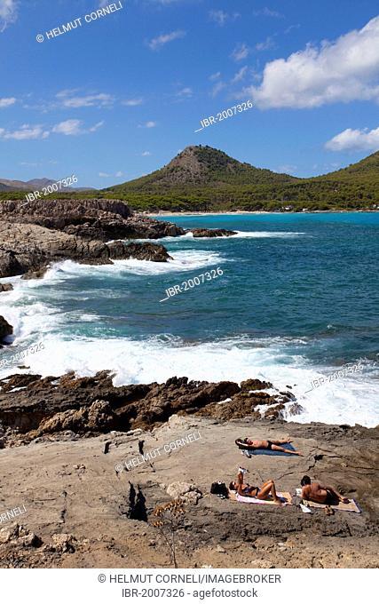 People lying in the sun on the rocky coast near the beach of Cala Agulla, Cala Guya in Castilian, Cala Ratjada, Majorca, Balearic islands, Spain