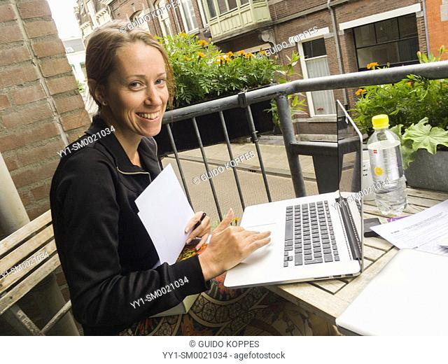 Tilburg, Netherlands. Adult blonde woman, working on her notebook computer while sitting at a balcony table, cooperating with a colleague
