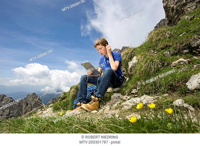 Teenage boy using iPad in mountain landscape