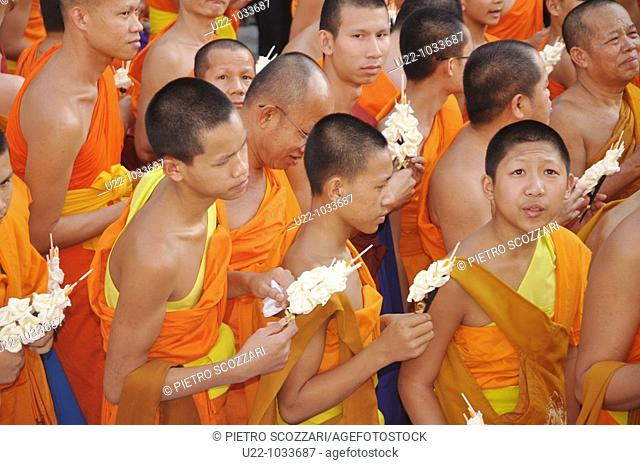 Chiang Mai (Thailand): young monks carrying paper flowers as offerings at the Wat Phra Singh during an important monk's funeral