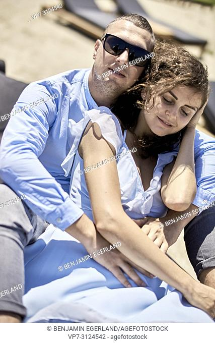 man embracing woman, on sunbeds, vacations, love, affair, sensual, couple, flirt, summer