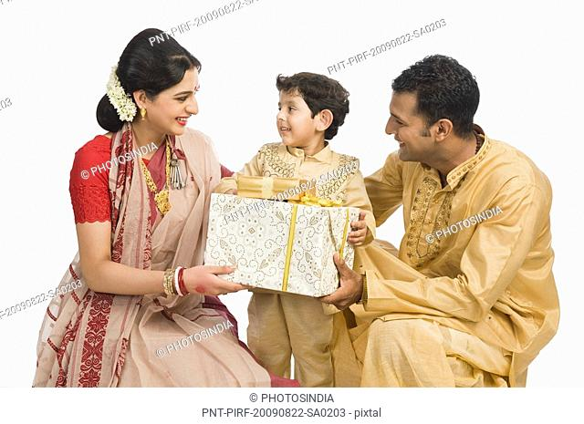 Family holding gifts at Durga Puja