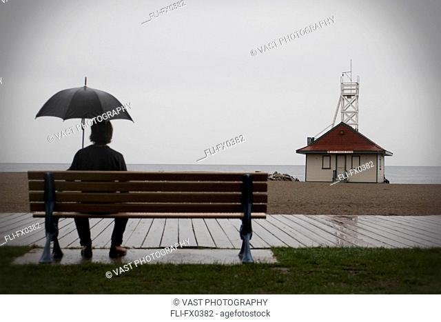 Man with Umbrella Sitting on Bench, Woodbine Beach, Toronto, Ontario