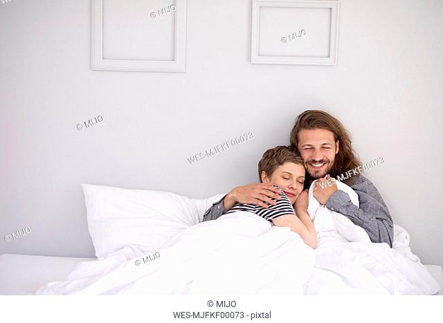 Happy young couple cuddling in bed at home