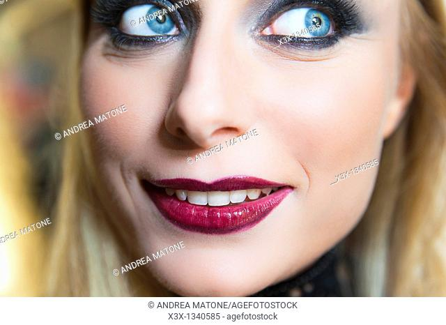Woman model with makeup looking away and smiling
