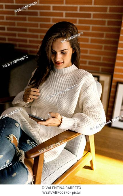 Young woman sitting on chair looking at cell phone