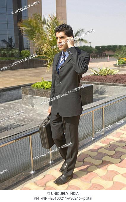 Businessman talking on a mobile phone, Gurgaon, Haryana, India