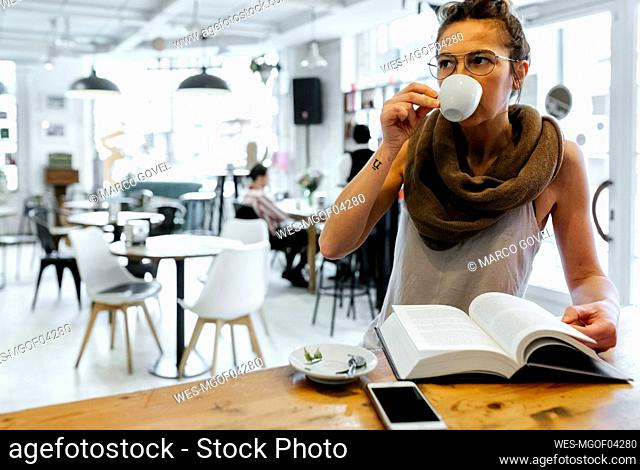 Woman reading book in coffee shop drinking coffee