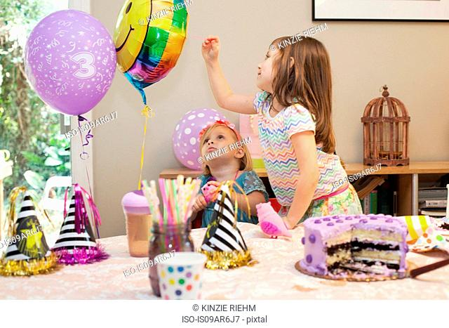 Two girls sitting at birthday party table with cake playing with balloons