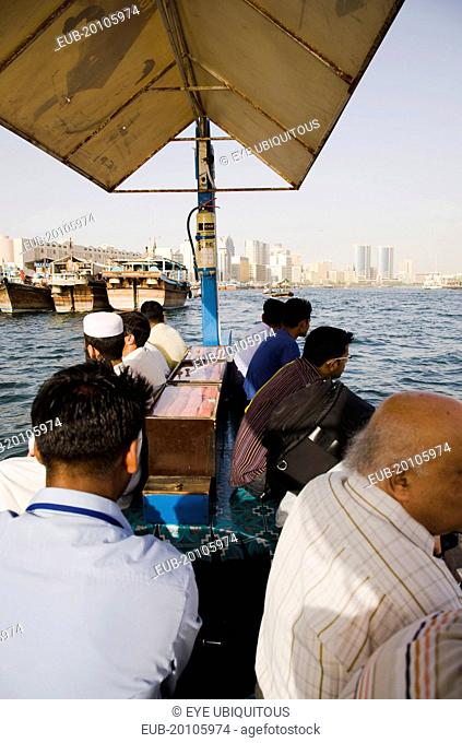Commuter passengers on Abra water taxi on the Creek with Twin Towers shopping mall and skyline behind