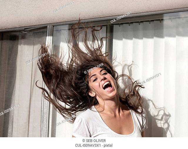 Young woman throwing hair back, in front of sliding doors