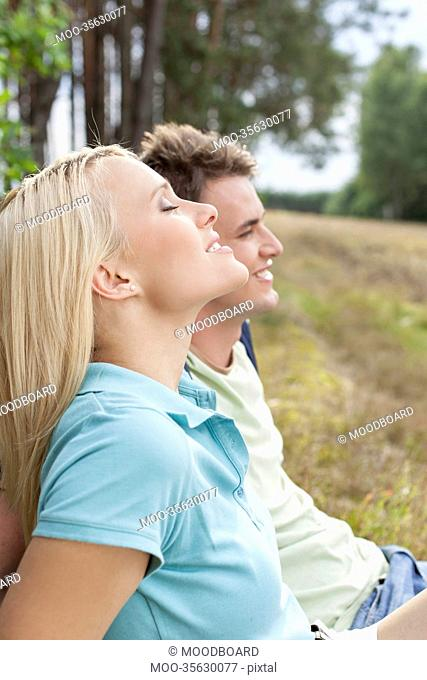 Beautiful young woman with eyes closed relaxing by man in forest
