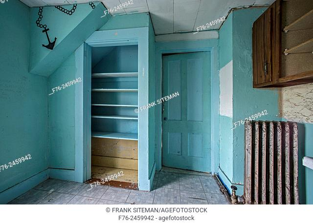 Empty teal colored room in an abandoned house with only a radiator and empty shelves