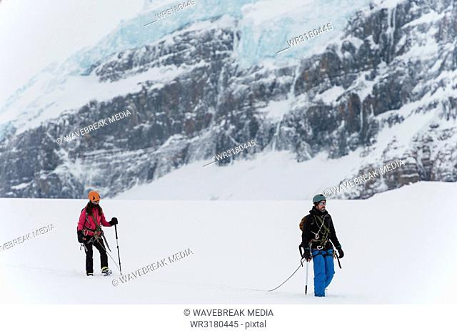 Couple walking with harness on a snow capped mountain