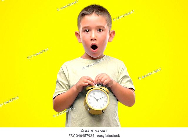 Little child holding alarm clock scared in shock with a surprise face, afraid and excited with fear expression