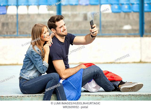 Young couple with French flag taking a selfie