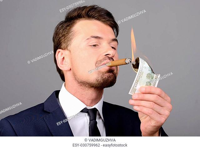 Rich businessman lighting cigar with $100 dollar bill