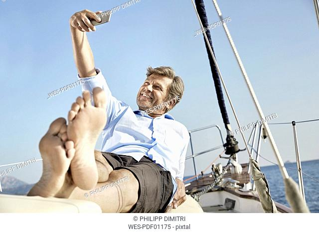 Smiling mature man lying on deck of his sailing boat taking selfie with cell phone