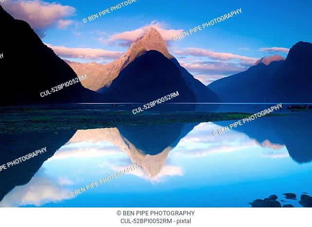 Rural mountains reflected in still lake