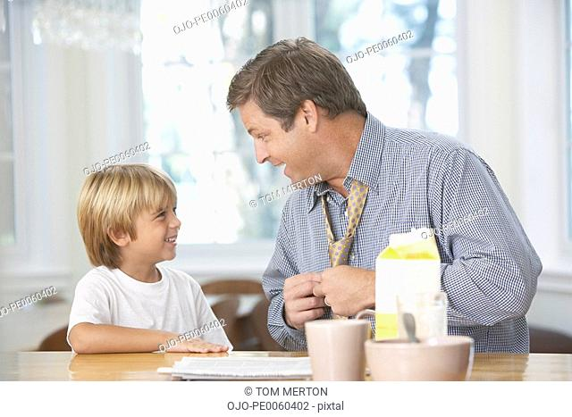 Man and young boy in kitchen bonding