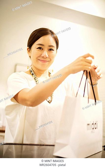 Woman working in a fashion boutique in Tokyo, Japan, holding shopping bag