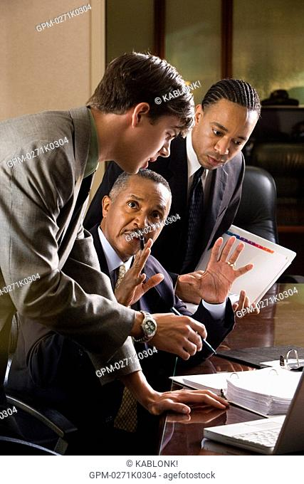 African American businessman with two young colleagues discussing business papers