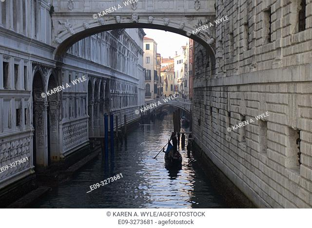 view of Rio di Palazzo under Bridge of Sighs, another bridge in background, gondola on canal, Venice, Italy