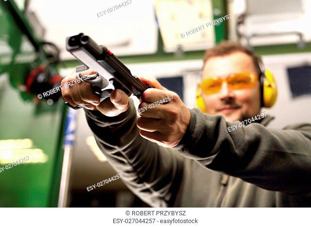 Strzelanie z pistoletu na strzelnicy. Mezczyzna na strzelnicy przeladowuje pistolet