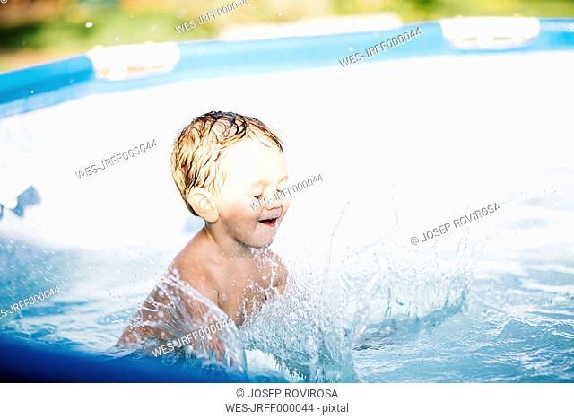 Little boy splashing in a paddling pool