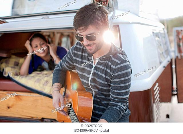 Mid adult man playing guitar at back of camper van, smiling