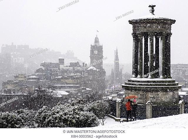 Snow falls on city of Edinburgh in December. Skyline view of city from Calton Hill, Scotland, UK